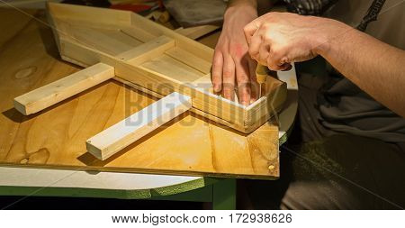 Male hands building model of a wooden ship.