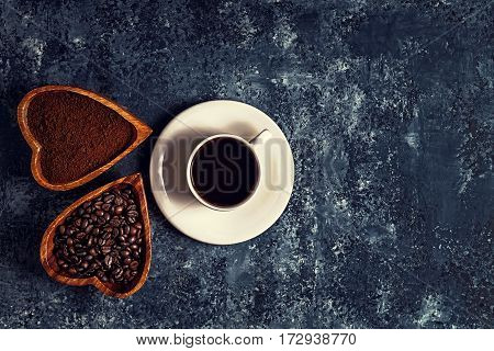 Coffee cup, beans and ground powder on stone background, top view.