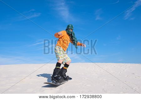 Man Snowboarding Amongst The Sand Dunes - Unusual Use