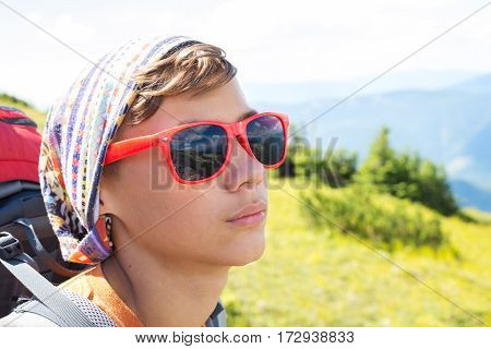 Portrait Of A Teenager In Red Sunglasses Which Reflect The Mountains And Clouds