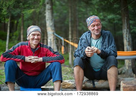 Joyful friends are relaxing in the camp and enjoying life during travel in the wild.