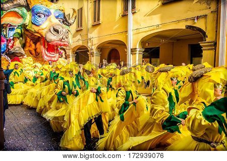Cento Italy 19 feb 2017: Carnevale di Cento colorful cow parade float with people choreography in yellow sunflower costumes