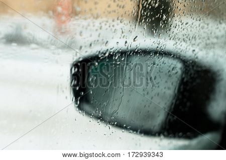 View from the car through the glass with drops of water in winter. Snow covered car window glass view from inside with mirror. Through raindrops on a car window is seen blurred rearview mirror