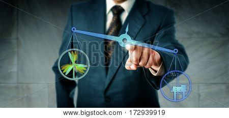 Business manager is touching a virtual balance on which an offshore oil and gas icon is lifting up a wind energy symbol. Energy industry concept for the relation between renewables and fossil fuels.