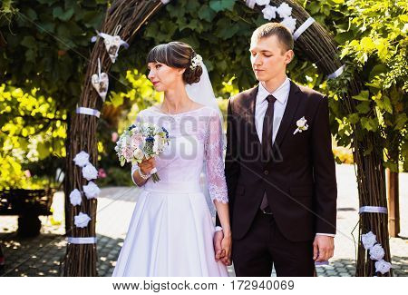 Groom and bride in white dress on background of the arch. Wedding ceremony. Happy family. The ceremony on the nature of the arch
