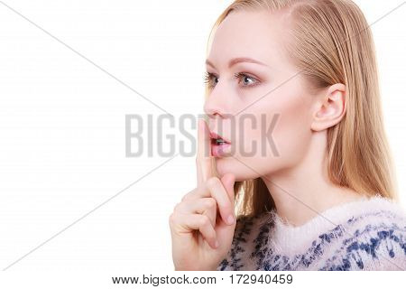 Gestures and signs concept. Young blonde woman making silence gesture with finger close to her mouth.