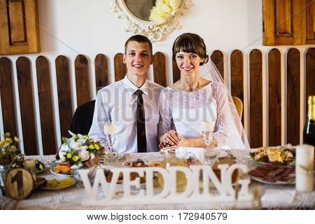 Groom and bride in a white dress in the restaurant. Wedding photography. Happy family in restaurant
