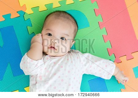 Portrait of a little adorable infant baby girl lying on back on colorful eva foam and looking in camera indoors