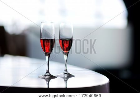 Two Glasses Of Wine Or Another Alcoholic Beverage On A Table