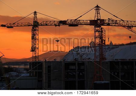 Construction crane on the orange sunset landscape.