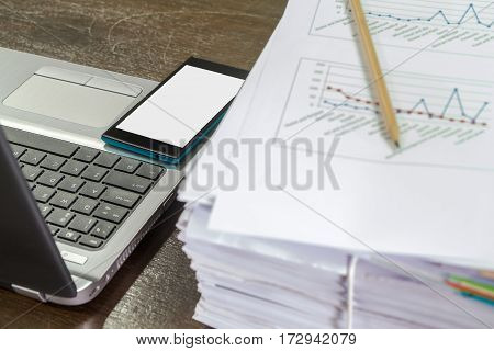 Smartphones On Laptop Near Documents Stack And Pencil