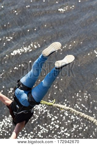 Girl tied a rope to jump off a bridge. Extreme sport