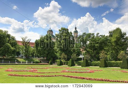 Blooming court garden in spring with church and trees in background. Kempten, Bavaria, Germany.