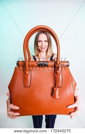 Woman holding brown leather handbag. Stylish girl showing bag. Female fashion vogue. Studio shot