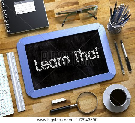 Learn Thai Handwritten on Blue Small Chalkboard. Top View of Wooden Office Desk with a Lot of Business and Office Supplies on It. Learn Thai on Small Chalkboard. 3d Rendering.