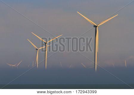 wind power turbines on a hill in fog. Dobrogea Romania