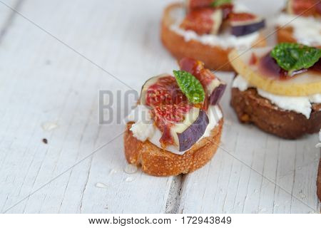 Bruschetta with goat cheese and figs on white wooden table