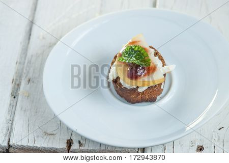 Bruschetta With Goat Cheese And Pear On White Plate