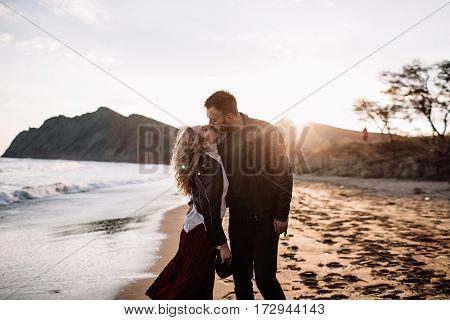 A Loving Couple Kissing On The Sandy Beach Near The Sea