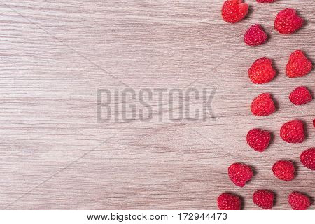 Red ripe raspberry lie on a wooden background. Copyspace flat lay top view. Flat lay raspberry