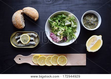 Vegetable salad with fish, healthy food, fish salad. salad at  black wooden background . Plate with green vegetables and herbs. Top view,