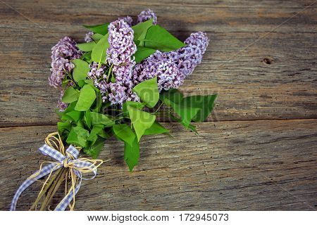 lilac bouquet tied with gingham and raffia bow on weathered wood