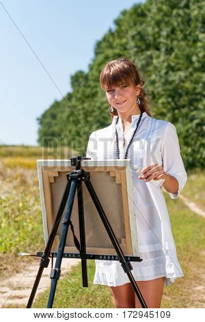Young woman artist at the easel painting landscape. Girl-artist working on the plein air.