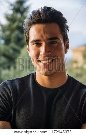 Headshot of handsome attractive young man smiling and looking at camera outdoor