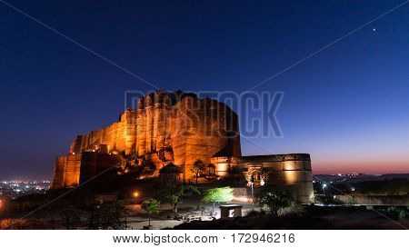 Glowing Cityscape At Jodhpur At Dusk. The Majestic Fort Perched On Top Dominating The Blue Town. Sce