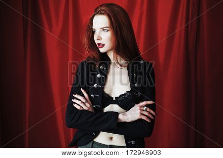Beautiful red-haired model with parted lips in black lingerie on red background looking away. Fashion photography. Bright appearance. Red hair model. Woman posing hands.  Model dressed in the style of fashion