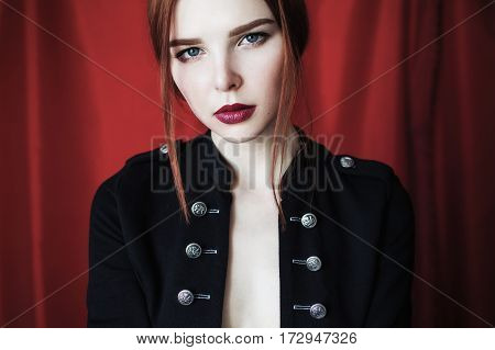 Beautiful redhead fashion woman in black unbuttoned jacket with red lips on red background looking at the camera. Fashion photography. Bright appearance. Red hair. Portrait of woman face on fashion style