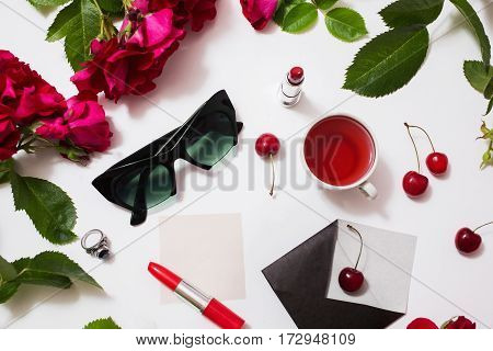 Frame of red beautiful roses with green leaves lady lipstick red tea black glasses a ring with a black stone envelope ripe cherries and a leaf of paper lie on a white background. Flat lay sun glasses