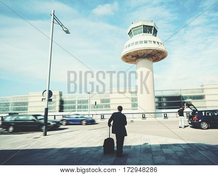 Rear view of businessman with luggage standing outside of airport in front of air traffic control tower and parking experienced male employer with suitcase waiting for taxi outdoors after work travel