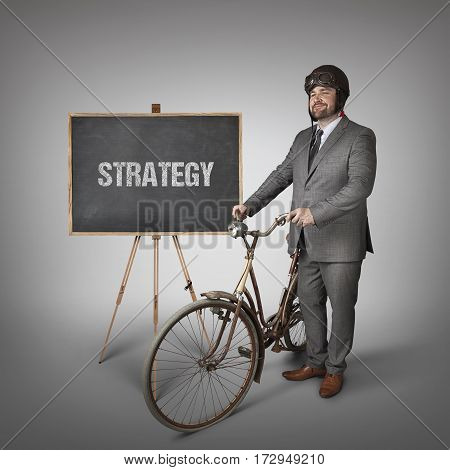 Strategy text on blackboard with businessman and vintage bike