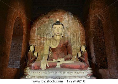 Ancient big Buddha statue sitting in meditation inside old pagoda in Bagan, Myanmar