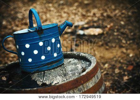 Blue Bin On Wooden Barrel