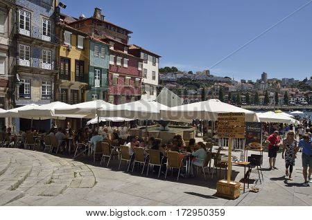 PORTO, PORTUGAL - AUGUST 5, 2015: People at an outdoors restaurant in the area of Ribeira one of the more typical places of the city of Porto Portugal.