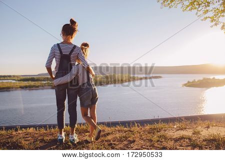sisters wearing denim clothing hugging  while looking at nature