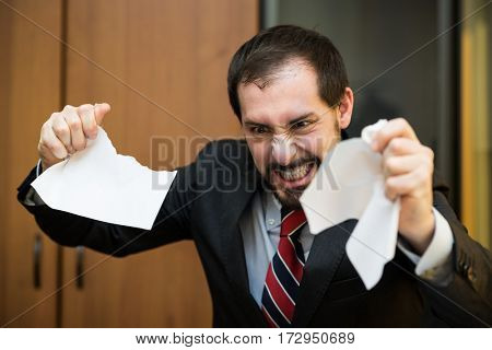 Angry businessman tearing apart a document in his office