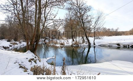 The quiet river quietly flows between snow-covered coast