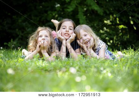 Three cute sisters smiling, playing in the park while they are laying. Happy family concept. Happy kids are resting together on the green grass.