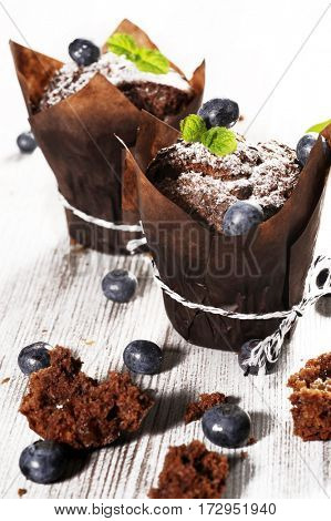 Chocolate dark muffin on a wooden table with blueberries and mint leaf on the top. Vintage food concept.