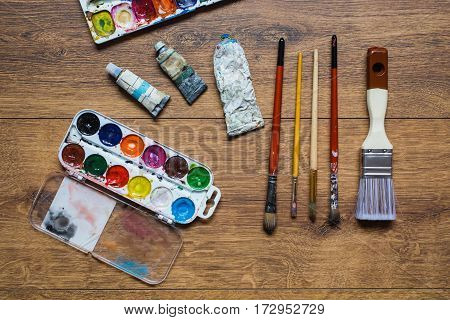 Artistic squirrel brushes tubes of oil paints and watercolors on a wooden background. Create art. The palette of twenty-four colors . Used tools for artists and schoolchildren. Tools for art. Set of art tools