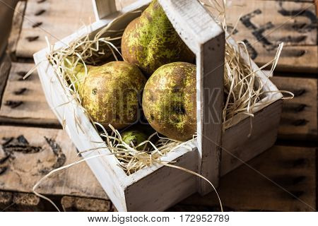 Heap of ripe organic conference pears in weathered wood box in straw natural light kinfolk style top view