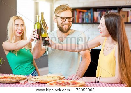 Young friends dressed casually in colorful t-shirts having having fun clinking bottles with beer and pizza at home