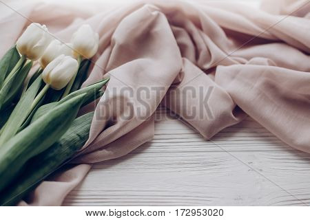 Hello Spring. Stylish White Tulips On Beige Soft Fabric On Rustic Wooden Table Background. Soft Ligh