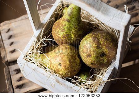 Top view of heap of ripe harvested conference pears in weathered wood box in rustic style soft daylight kinfolk style