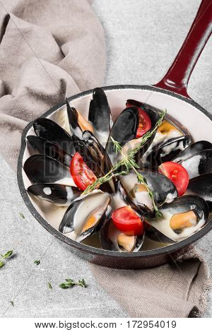 Cooked mussels in a pan served on a napkin garnished with tomatoes and thyme. Steamed mussels in white wine sauce. Seafood mussels on pan with cream sauce. Close up.