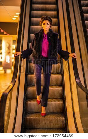 Beautiful sexy girl in stylish fashionable clothes posing on stairs