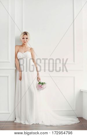 Classical young gourgeous bride. Studio interior fashion shot of fashion smiling model in wedding dress with bouquet of flowers posing in white room. Blonde woman portait with profeshional make-up and hairstyle.